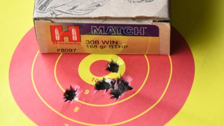 A close up of bullet holes in a paper target with a box of ammunition behind, showing a sub MOA string
