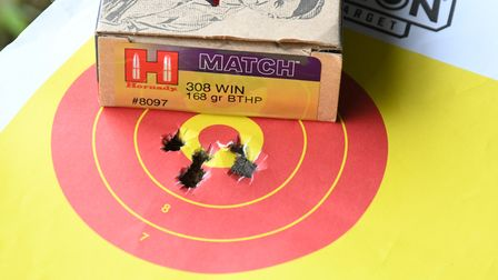 A close up of bullet holes in a paper target with a box of ammunition behind, showing close group