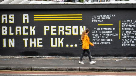 A woman looks at a graffiti art piece on Black Lives Matter on a wall in the Stokes Croft area of Br