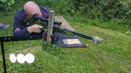 Gary Chillingworth shooting an air rifle in the prone position in a garden; inset image of three white targets