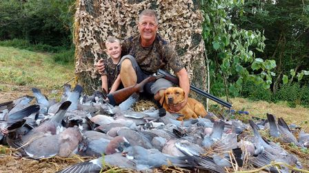 Andy Crow, his grandson Regan and dog Rosa with a pile of shot woodpigeons in front of a pigeon shooting hide