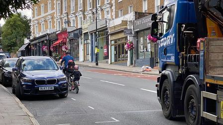A lorry prior to passing a family bicycle on Haverstock Hill