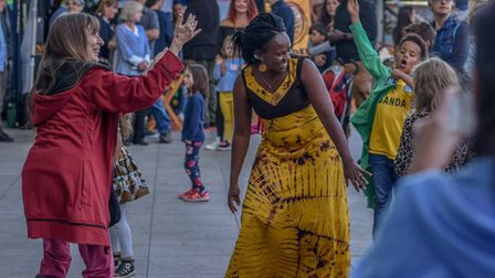 Visitors to Norwich's African and Caribbean Market dancing with a performer, at the The Forum