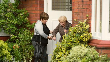 Carer helps client down her front door step at Right at Home, Weston-super-Mare
