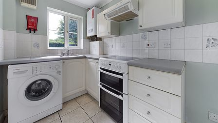 the white cupboards in the kitchen with washing machine and oven