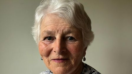 A headshot of Diney who is smiling at the camera. She has rosy cheeks and silver white hair.