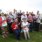 Saffron Walden U3A members laying musical instruments, outside on grass. Essex