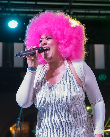 Woman singing into microphone on stage, pink wig, Dance in the Square, Saffron Walden, Essex, August 2021