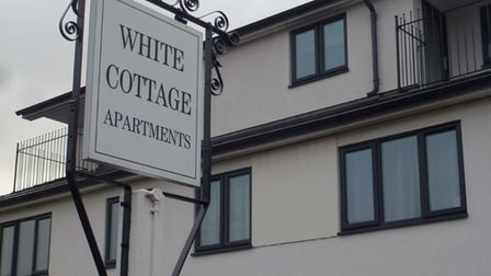 A sign which would have once signalled the White Cottage pub was repurposed when it became White Cottage Apartments.