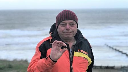Steve Sandeel holding the engraved ring of Ingrid Fletwood, that he found on Overstand beach after h