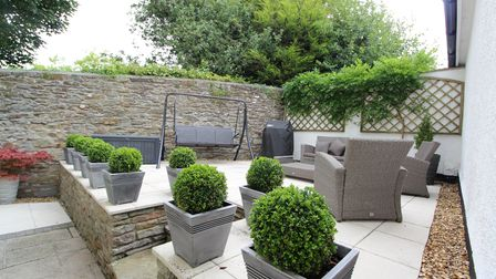 The patio at the detached house in High Street, Nailsa, has cream square slabs, pots with box bushes and step down to garden