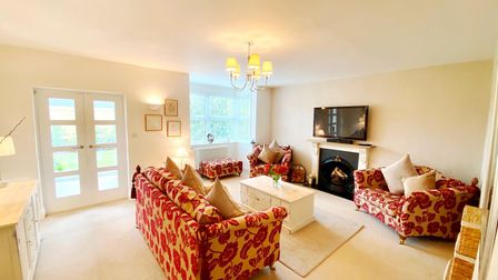 Sitting room in the High Street, Nailsea, house with cream walls and carpet, patterned sofas and cast-iron fireplace