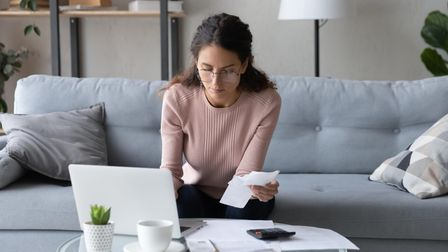 Serious young woman in glasses sit in living room pay bills taxes on laptop online, focused millenni