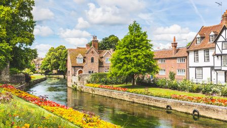 View of typical houses and buildings in Canterbury, England. Flowers and trees along the canal in su
