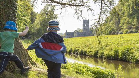 Children playing around a tree in Spring time, with a view of Fountains Abbey in the distance, North