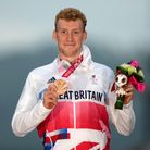 Paralympian George Peasgood stands atop a podium holding up his bronze medal and a bouquet at Tokyo 2020