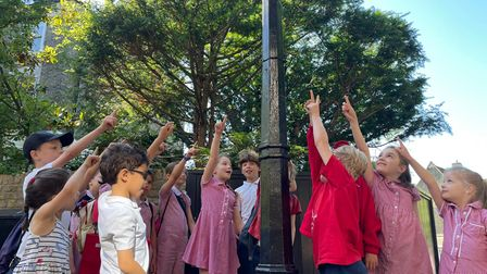 Kids pointing to a pollution monitor installed in July