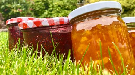 Full pots of jam and marmalade without labels on