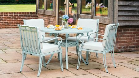Four metal framed outdoor chairs with cushions are positioned around a circular table