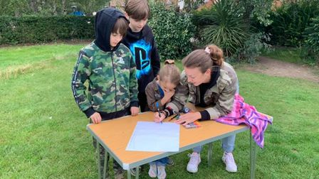 A family jotting down their ideas for the Cooper Road play park in Sheringham.