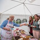 A woman in an apron hands cake to a group of four people at Stansted Windmill Fete, Essex