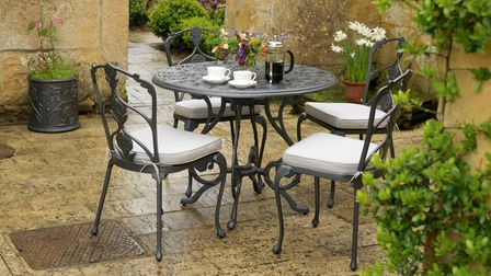 Black, ornate metal chairs surround a circular table with cups and a cafetiere on it