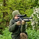 Phil Siddell taking a kneeling shot with an air rifle, in British woodland
