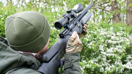 Phil Siddell taking a shot in woodland with an air rifle, photo taken from behind, Phil is shooting up into the trees