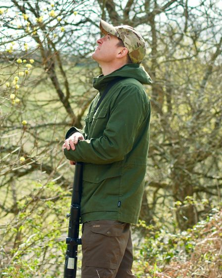 Phil Siddell stood with an air rifle, gazing upwards as if waiting