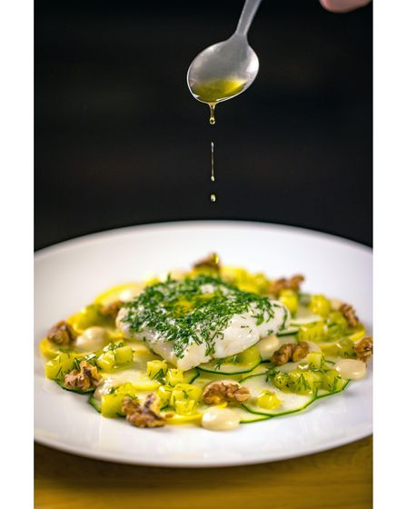 A fish dish, with leeks and walnuts, with a spoon pouring olive oil