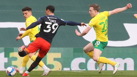 Thomas Ince of Luton Town has a shot on goal despite the efforts of Max Aarons of Norwich, Oliver Sk