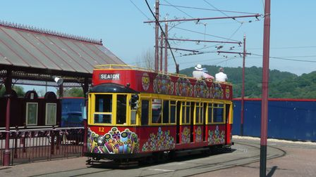 A red tram sits in front of the station