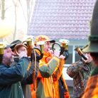 A group of European hunters blowing hunting horns at a driven hunt ceremony