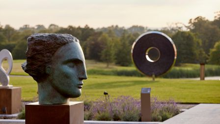 Sculpted head and large disk with central hole sculptures