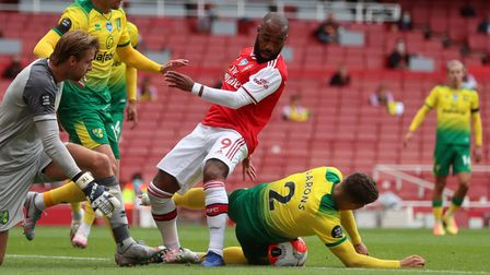 Arsenal's Alexandre Lacazette is tackled by Norwich City's Max Aarons (right), Tom Trybull and Tim K
