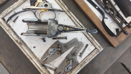 Elements of a shotgun in a tray on a work bench in the TR White gunmakers