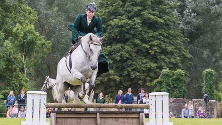 A side saddle rider on a horse tackles a jump at Audley End House and Gardens, Essex