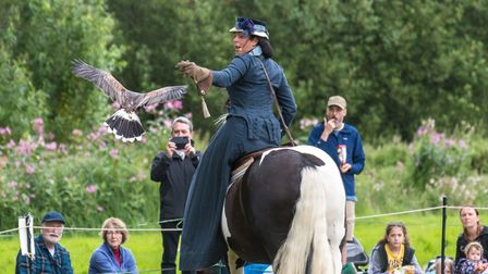 A bird of prey flies to a handler who is seated on a horse, Audley End House and Gardens, Essex