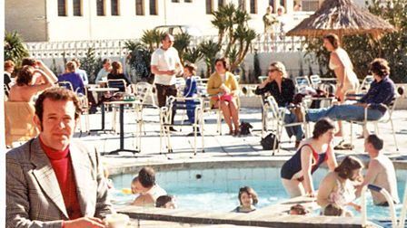 The secretary waits by the pool as the others jump in.