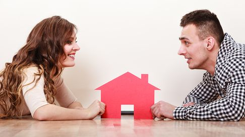 Happy couple lying on the floor face to face looking at each other and holding paper red house