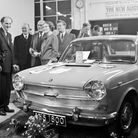 Mr. and Mrs. S.O. Kingcott and some of their customers gathered round the new Austin 1800 at a party