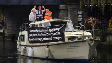 Annie Holgate, 81, right, with her dog Buttons, displaying her protest banner as she cruises up the