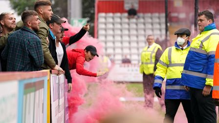 Swindon Town fans are spoken to by stewards as they throw objects towards the pitch during the League Two match at Stevenage.