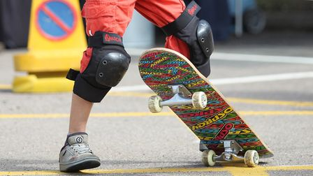 A person wearing orange trousers and knee pads stands on a skateboard. Picture: Danny Loo