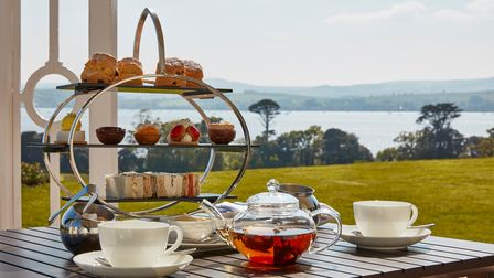 A Devon cream tea being served outside overlooking the sea.