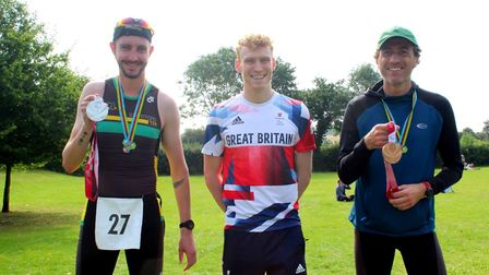 Two triathletes from Bishop's Stortford hold up George Peasgood's Tokyo 2020 Paralympic medals
