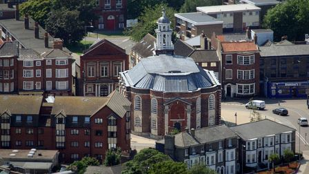 An aerial view shows the full building which is octagonal with red brick and a tower