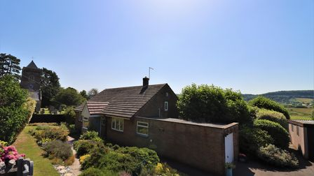 Dark brown bungalow in Weston-in-Gordano with garage lengthways on the side with raised front garden and country views behind