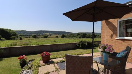 patio at the back of the bungalow in Clevedon Road, Weston-in-Gordano with patio furniture, lawn, wall and fields beyond