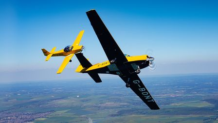 Two yellow planes flying in a synchronised air display